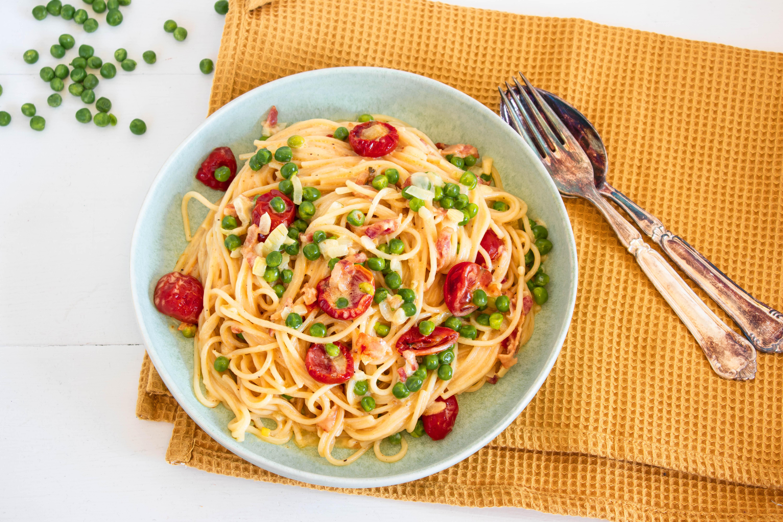 Cremet pasta med ærter, bacon og tomater