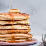 Lækre luftige amerikanske pandekager med ahornsirup og smørklat
